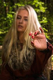 foto of rune  - Scandinavian witch pythoness with runes on a forest background  - JPG