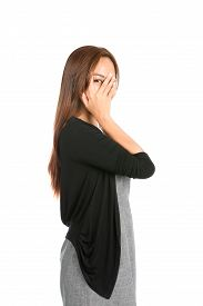 foto of shy woman  - Profile of gorgeous Asian woman in casual clothes sweater and dress hand covering face eye peeking through split finger showing shy fearful emotion - JPG