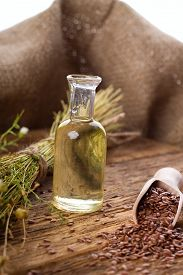 stock photo of flax seed oil  - Vertical photo of flax seeds in wooden spoon and flax oil in small bottle - JPG