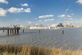 picture of passenger ship  - A large refinery with gas storage tanks in the port of Antwerp Belgium with lots of distillation towers and a jetty in the foreground - JPG