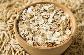 foto of oats  - Rolled oats and oats in a wooden bowl - JPG