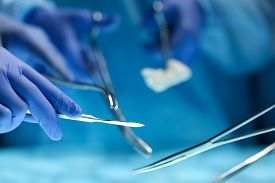 foto of surgical instruments  - Surgeons hands holding surgical instrument while operating patient in surgical theatre - JPG