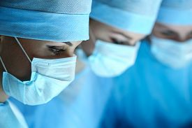 image of resuscitation  - Three surgeons at work operating in surgical theatre - JPG