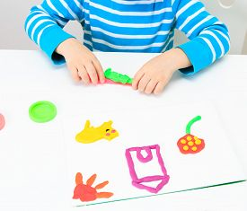 stock photo of daycare  - little boy playing with clay dough - JPG