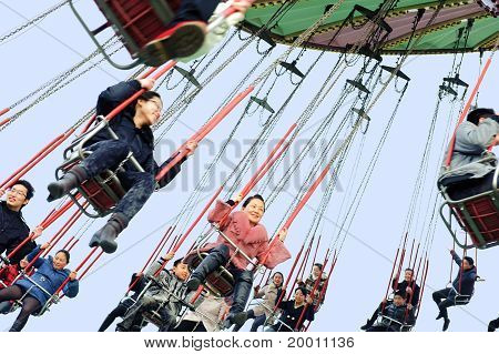 Happy people play on chairoplane
