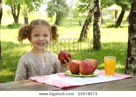 little girl with fruit and juice in park