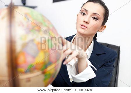Businesswoman In Office Looking Globe