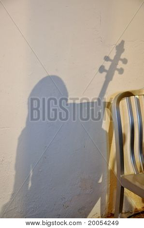 Shade of the woman with a musical instrument and a chair at a white wall
