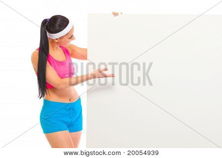 Fit girl in sportswear looking and pointing on blank billboard isolated on white