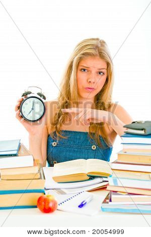 Worried teen girl sitting at table with books and pointing finger on alarm clock
