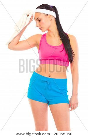 Tired young girl wiping her face with towel after exercising isolated on white