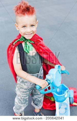 f88f783ee9e27 Happy little child playing superhero. Kid having fun outdoors. Kid  superhero in a red