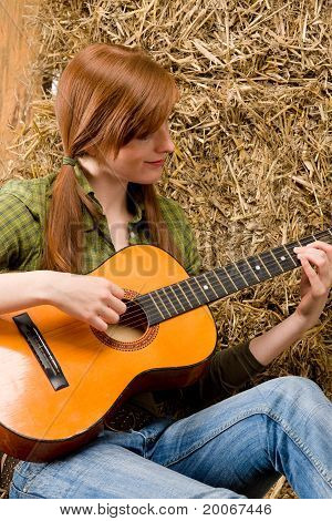 Young Country Woman Playing Guitar In Barn