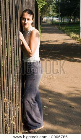 Woman Near A Fence