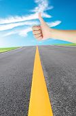 image of road trip  - thumb up hand sign of woman for stops the car on the road under blue sky - JPG