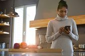 Young woman using phone in kitchen at home poster
