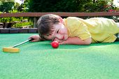 image of miniature golf  - Young boy plays mini golf on putt putt course - JPG