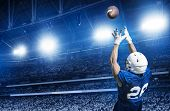 American Football Player Catching a touchdown Pass in a large stadium. poster