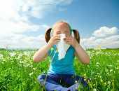 image of cute little girl  - Little girl is blowing her nose while sitting on green meadow - JPG