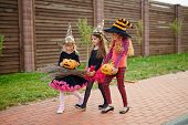 Little halloween witches in hats moving down pavement during trick-or-treat promenade poster