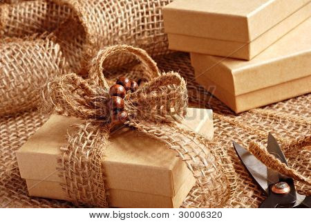 Gift wrapping still life with small brown boxes being decorated with eco friendly burlap ribbon and tiny wooden beads.  Macro with shallow dof.