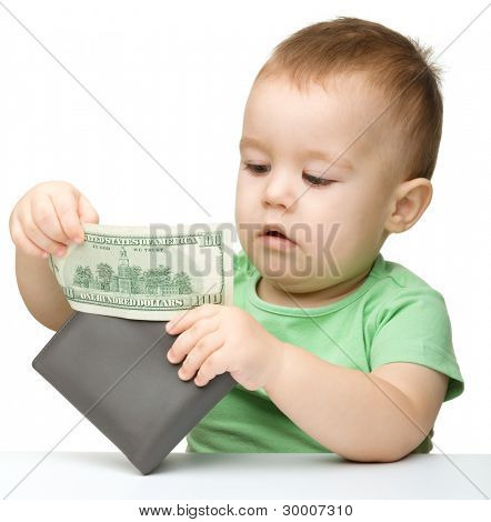 Cute little boy is playing with paper money - dollars, isolated over white