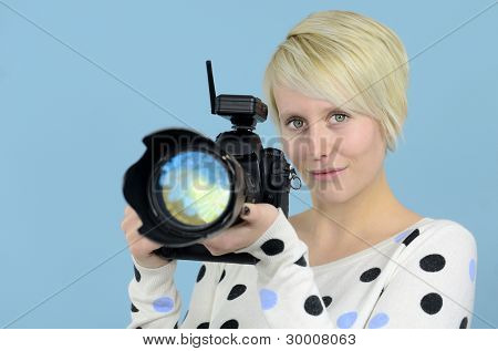 young female photographer with D SLR camera on blue background