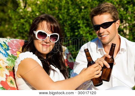 Couple in love drinking beer in summer in the garden and enjoy
