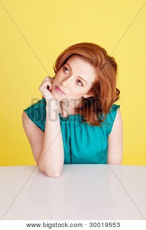 Beautiful redhead woman seated at a table with her chin on her hand lost in deep thought.