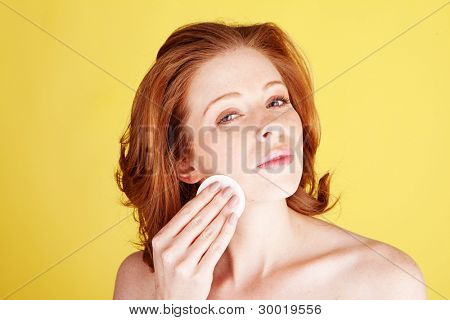 A beauty shot of an attractive redhead woman cleaning her face with a cotton pad