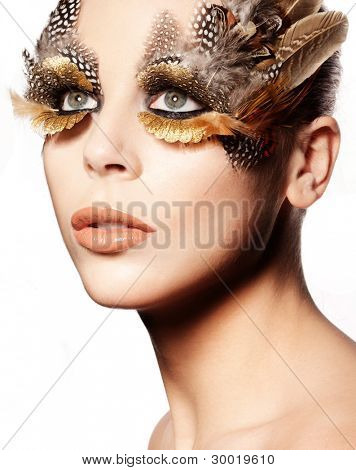 Closeup portrait of a beautiful woman wearing striking creative eye makeup with birds feathers.