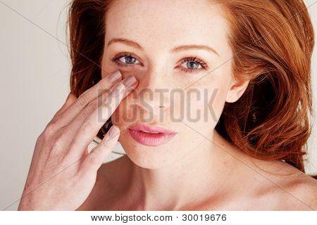 attraktive Rothaarige Frau in Portrait schönheit Mischung auf ihr Gesicht mit den Fingerspitzen-Stiftung