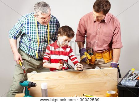 Little boy trying his best in a woodshop being looked after by his dad and grandfather