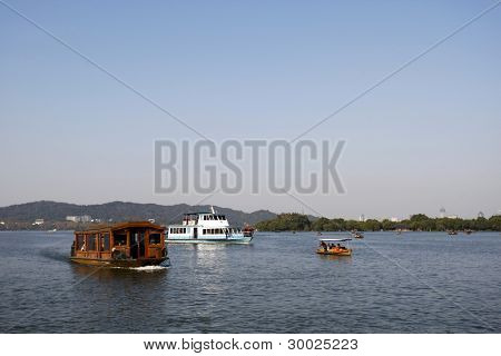 HANGZHOU, CHINA - NOVEMBER 26: Visitors take a ferry cruise on the infamous West Lake on November 26, 2011 in Hangzhou, China. It was made a UNESCO World Heritage Site in 2011.