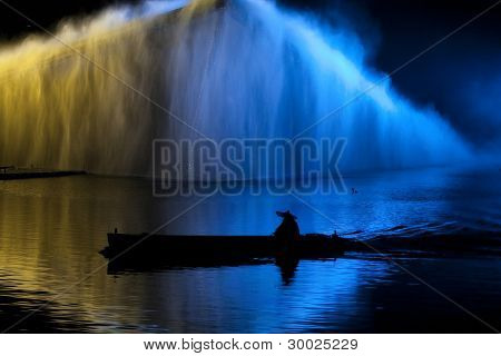 HANGZHOU, CHINA - NOVEMBER 26: An actor in a boat performs in Zhang Yimou's folk musical show 'Impressions West Lake' in an outdoor theatre built in the lake on November 26, 2011 in Hangzhou, China.