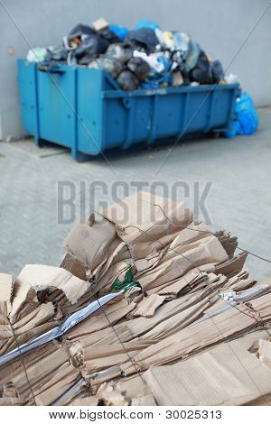 tied,segregated cardboard at the front and waste containers with nonsorted wasted in bags at the back - out of focus