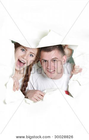 young couple getting out from hole in paper