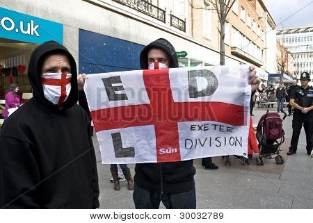 Exeter English Defense League members hold up their EDL St George flag