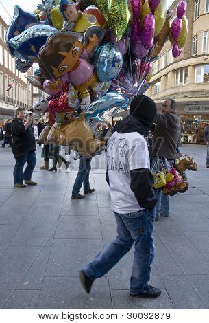 Non- English Defense League member walks passed a balloon seller