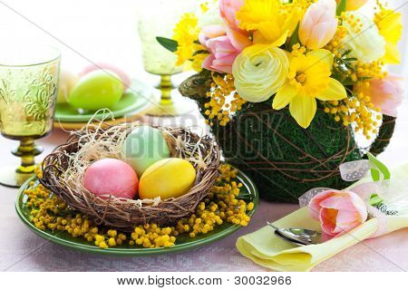 Easter table setting with colored eggs and spring flowers
