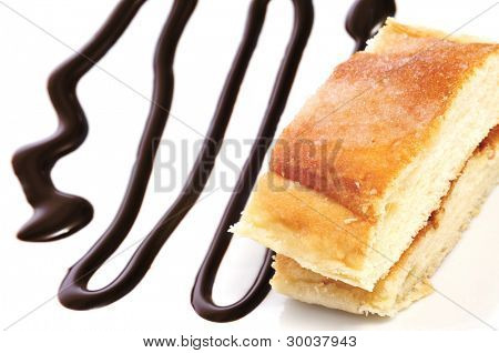 some slices of coca amb sucre, a typical catalan cake, with chocolate syrup