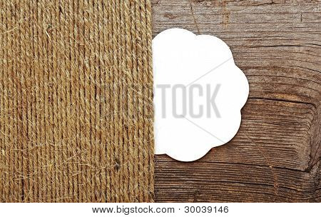 blank tag and old ropes over wooden background. space for your text