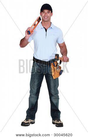 Builder holding spirit level and hammer