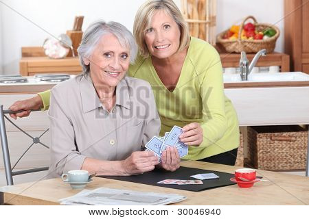 Two mature women playing cards.