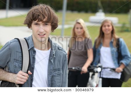 Young man standing in front of two girls with bikes
