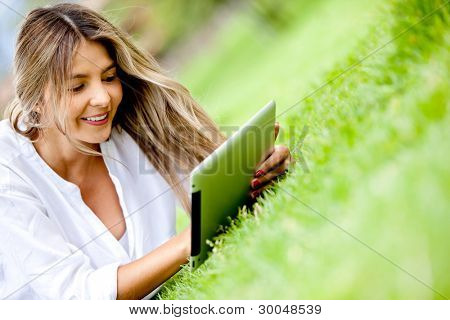 Woman using a tablet computer outdoors - technology concepts
