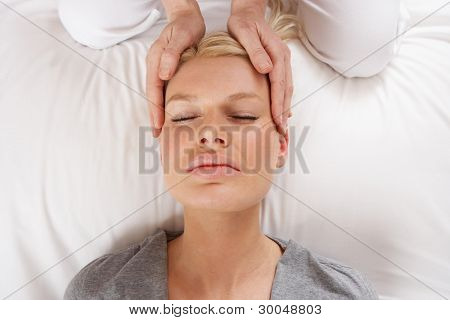 Woman having Shiatsu massage to head