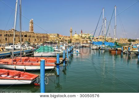 Yachts and boats at old harbor against ancient walls of historic town of Acre (Akko) in Israel.