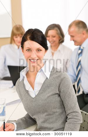 Young executive woman take notes during meeting with team colleagues