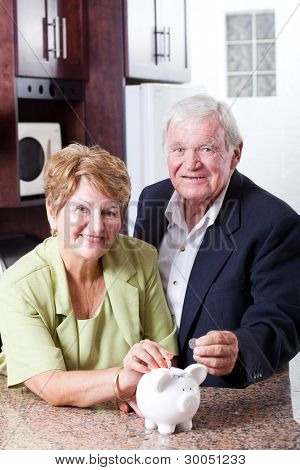 retirement savings concept: senior couple putting coins in piggybank